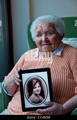 98 years old elderly lady holding an iPad tablet computer, displaying a sepia portrait of herself taken 80 years - Stock Photo