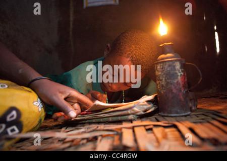 A student studies by the light of a kerosene lamp in Masaka, Uganda, East Africa. - Stock Photo