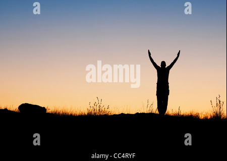 Man standing with raised arms in the indian countryside at dawn. Silhouette - Stock Photo