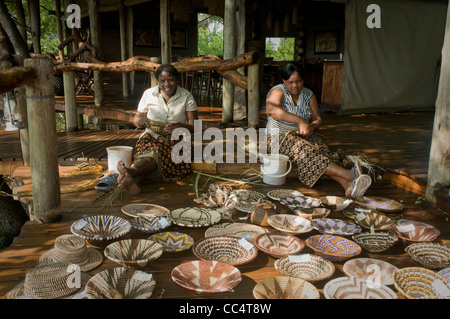 Africa Botswana Tuba Tree-Women weaving baskets, showing baskets in foreground - Stock Photo