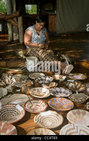 Africa Botswana Tuba Tree-Woman weaving basket, showing baskets in foreground - Stock Photo