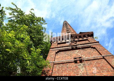 Smokestack of an old abandoned industrial complex - Stock Photo
