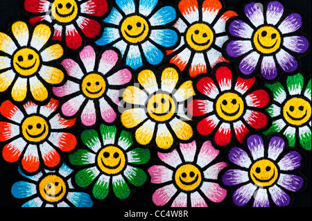 Embroidery iron on patches of Multicoloured smiley face flowers on a black background - Stock Photo