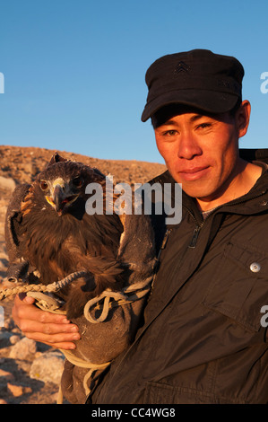 Kazakh eagle hunter and his golden eagle in the Altai Region of Bayan-Ölgii in Western Mongolia - Stock Photo
