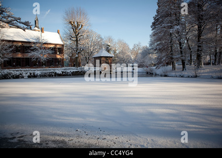 The lake at Walburgh park in Sint-Niklaas frozen and covered snow - Stock Photo