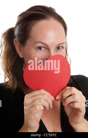 Woman Holding Red Paper Heart over face below eyes - Stock Photo