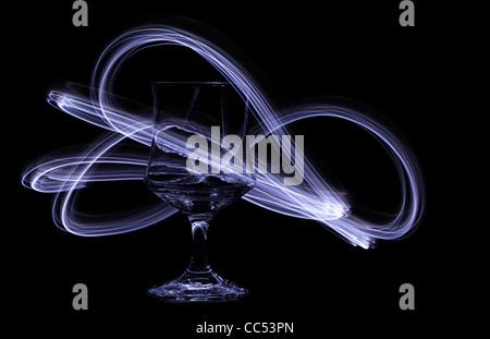 Swirling light trails dance around a glass chalice. - Stock Photo