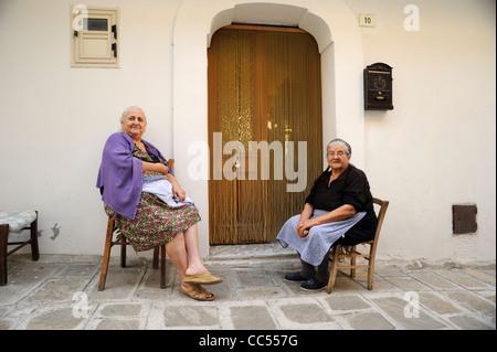 italy, basilicata, roccanova, old italian women outside house - Stock Photo