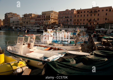 small working fishing boats moored stern first in Anzio harbour - Stock Photo