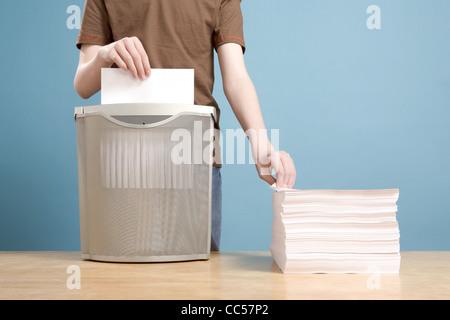 Teen Boy Shredding Stack of Paper - Stock Photo