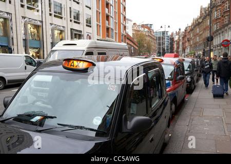 row of london black taxis on brompton road knightsbridge London England UK United kingdom - Stock Photo