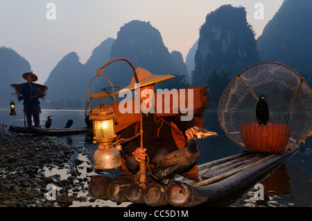 Chinese fishermen with cormorants at dawn on the Li river and tall karst formation mountains Yangshuo China - Stock Photo
