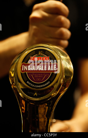 A beer tap displays the English India Pale Ale beer logo - Stock Photo