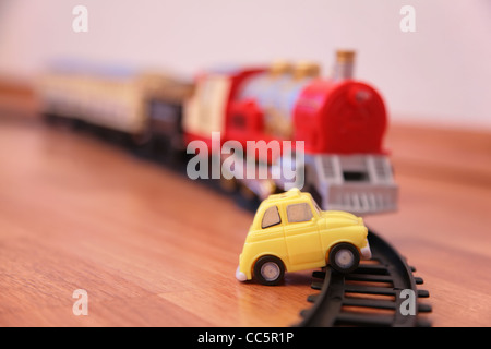 Red toy train and yellow toy car on railroad - Stock Photo