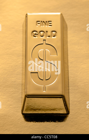 Gold Bar with a Dollar symbol embossed on it on a gold background - Stock Photo
