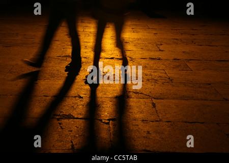 people walking in street at night - Stock Photo