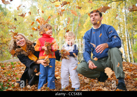 family of four throw autumnal leaves - Stock Photo