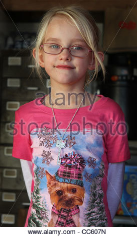 A close up of a six year old girl wearing glasses. - Stock Photo