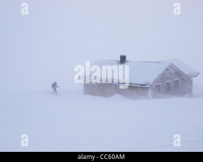 A ski-tourer reaches the safety of a mountain hut in a blizzard, Norway - Stock Photo