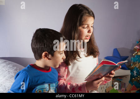 Close-up of siblings reading bedtime stories together - Stock Photo