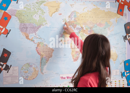 Young girl pointing to different countries on the world map - Stock Photo