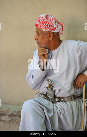 An Omani man proudly shows is prized khanjar, the traditional curved dagger, in the rifle and khanjar market in - Stock Photo