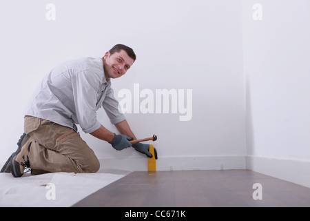 a man laying floorboards - Stock Photo