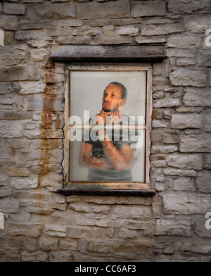 African American young man looking out of window during rain - Stock Photo