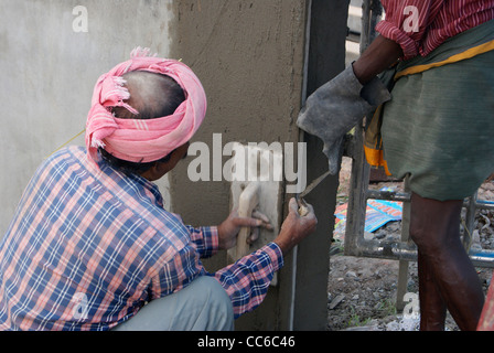 Masonry worker (Mason) plastering and polishing wall with cement - Stock Photo