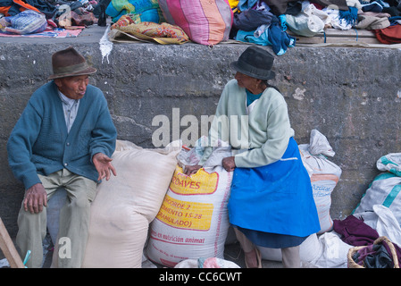 An elderly man and wife of Andean Indian descent sit on sacks of grain in the famous market town of Saquisili, Ecuador. - Stock Photo
