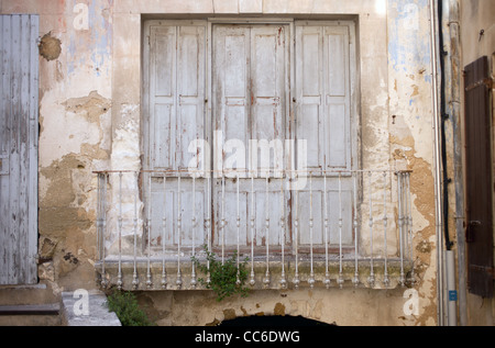 Three old wooden doors open up to a metal balcony railing in Menerbes, France - Stock Photo