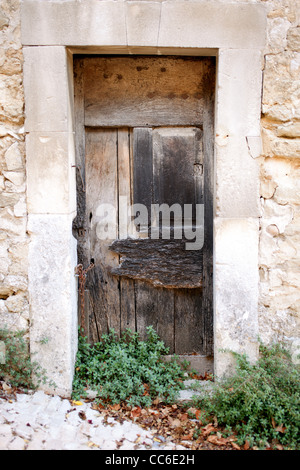 An old wooden door sits inside of a stone frame on a building in Menerbes, France - Stock Photo