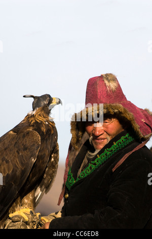 An old Kazakh eagle hunter with his Golden eagle. - Stock Photo