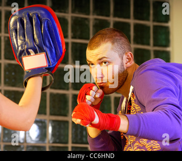 young adult man boxing in gym with his trainer - Stock Photo