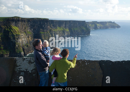 Family enjoying the view at the Cliffs of Moher, The Burren, County Clare, Ireland. - Stock Photo