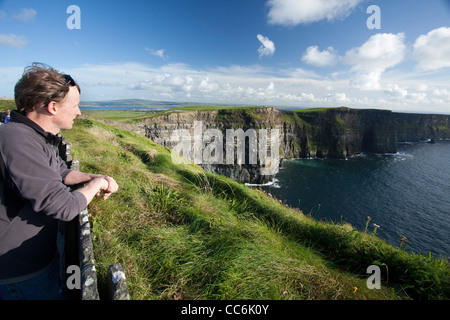 Tourists enjoying the view at the Cliffs of Moher, The Burren, County Clare, Ireland. - Stock Photo