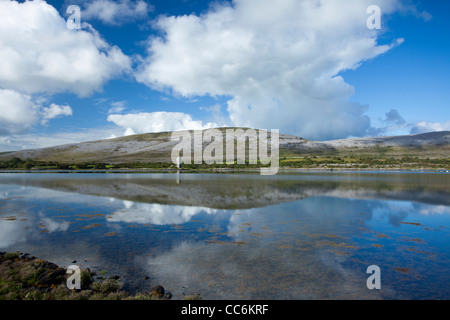 The limestone landscape of The Burren reflected in Ballyvaughan Bay, County Clare, Ireland. - Stock Photo