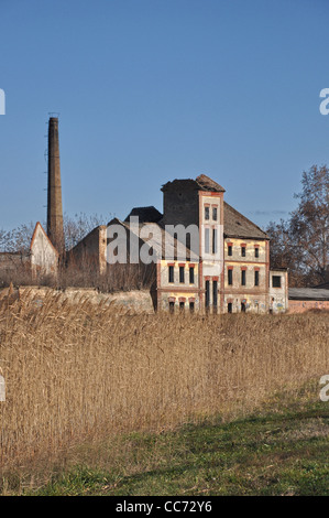 Old factory ruined exterior on a sunny day - Stock Photo