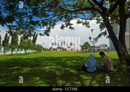 Indonesia, Sumatra, Banda Aceh, couple under tree in front of Baiturrahman Grand Mosque (Mesjid Raya Baiturrahman) - Stock Photo