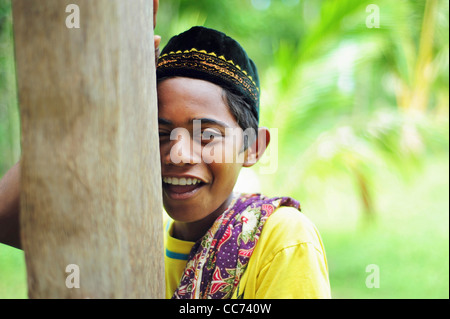 Indonesia, Sumatra, Banda Aceh, young boy in traditional dress smiling and hiding behind tree - Stock Photo