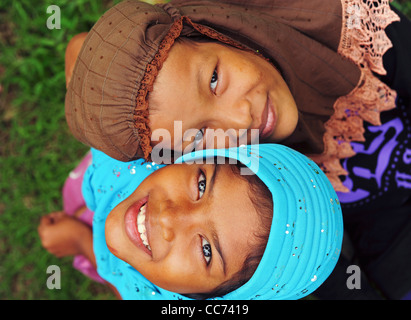 Indonesia, Sumatra, Banda Aceh, two smiling girls looking up with colorful veils - Stock Photo