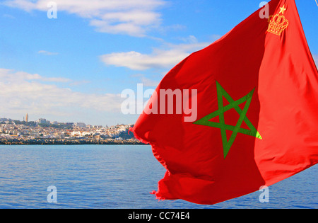 The Moroccan flag in foreground and the city of Tangier in background seen from the ferry to Tarifa, Morocco. - Stock Photo