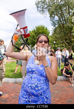Female protester speaking through a bullhorn - Stock Photo