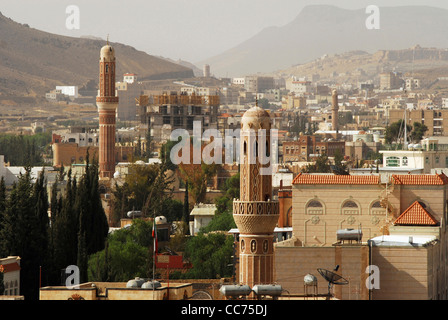 Yemen, Sanaa, elevated view of tall ancient brown minarets with cityscape and mountains in the background - Stock Photo