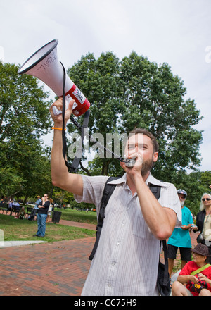 Protester speaking through a bullhorn - Stock Photo