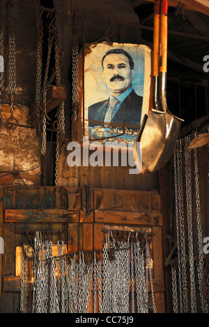 Yemen, Sanaa, chains and spades hanging in wooden store with portrait of President Saleh - Stock Photo