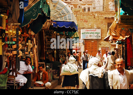 Yemen, Sanaa, people walking in busy street market by shop with building in the background - Stock Photo