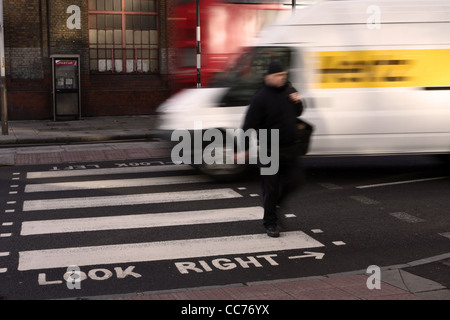 a blurred figure of a man walks across a zebra crossing in London while a van passes behind