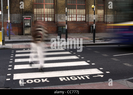 a blurred figure walks across a zebra crossing in London