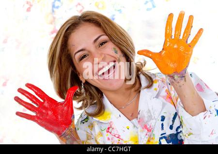 Messy Hispanic woman finger painting - Stock Photo